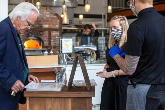 A Ritter's employee takes a to-go order in downtown Salem on May 22, 2020.