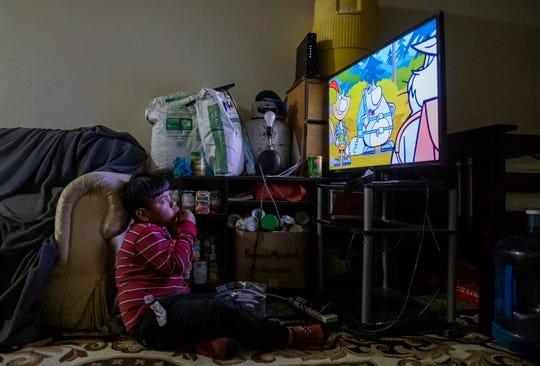 Hugo Salvador come una cereza directo de la bolsa mientras ve la televisión. Detrás de Hugo está la pila de alimentos enlatados no perecederos que ha recibido la familia Salvador en diferentes eventos de distribución de alimentos.
