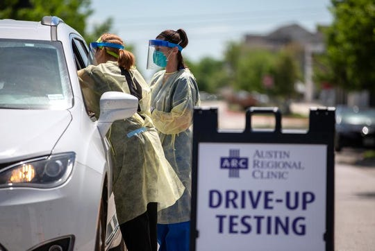 Nurse Kristen Howell, left, and medical lab tech Amanda Hernandez administer a coronavirus test at the Austin Regional Clinic drive-thru testing site in Kyle.