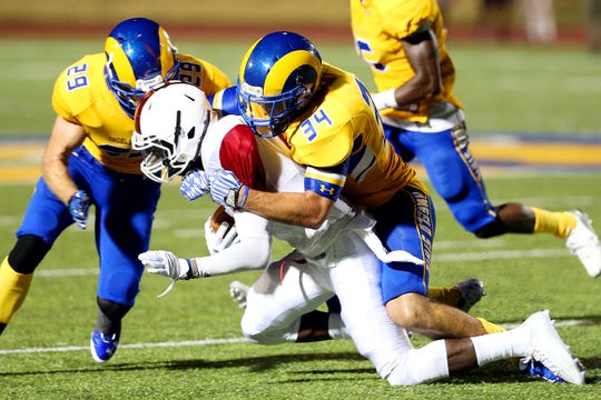 Angelo State's Grant Aschenbeck (34) brings down an Oklahoma Panhandle State ball carrier in a 2015 game.