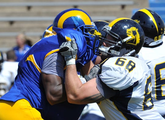 Angelo State's Lawrence Rumph battles through the holding of Central Oklahoma's Justin Pruitt in a game Sept. 17, 2011.