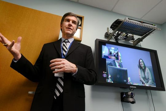 Atlantic General Hospital President and CEO Michael Franklin demonstrates the telemedicine system installed at the Atlantic Health Center in Berlin in this file photo. On the screens are doctors from the Kennedy Krieger Institute in Baltimore.