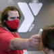 Cordell Ring, an employee with the Aberdeen Family YMCA, left, uses a scanning thermometer to take to the temperature of a member before they enter the facility.
