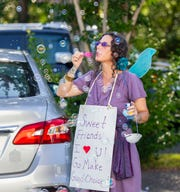 SAIL High School health, adulting, and yoga teacher Susanna Denham blows bubbles as seniors pass by in their cars Thursday, May 21, 2020.