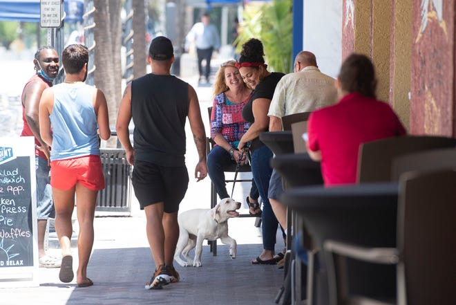 Deb Martin (center), of Jensen Beach, and Mel Bello (third from right), of Port St. Lucie, coworkers at Healthy Start Coalition of St. Lucie County, along with Bello's dog, Otis, pick up lunch from 2nd Street Bistro on Friday, May 22, 2020, in downtown Fort Pierce.