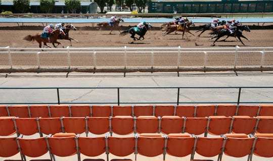 The field of quarter horses dash past empty stands Friday at Ruidoso Downs. The 2020 racing season is underway at Ruidoso Downs Racetrack in Ruidoso, N.M. after live racing was halted in mid-March because of COVID-19. The track is starting the season without fans in the stands due to the coronavirus.