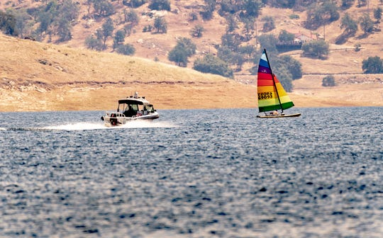 Tulare County Sheriff Deputies head out for patrol as Brad Anderson of Lemoore sails his Hobie Cat 16 on Lake Kaweah on Friday, May 22, 2020. The marina reopened today after closing amid COVID-19 concerns.