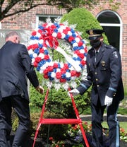 Police officers from Clarkstown place a wreath Police during the annual Clarkstown Memorial Day Tribute at the Promenade of Heroes in New City May 22, 2020.