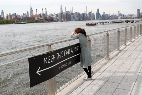 A young girl peers out at the East River with the Manhattan skyline as a backdrop as she relaxes on the boardwalk at Brooklyn's Domino Park during the current coronavirus outbreak, Monday, May 18, 2020, in New York.