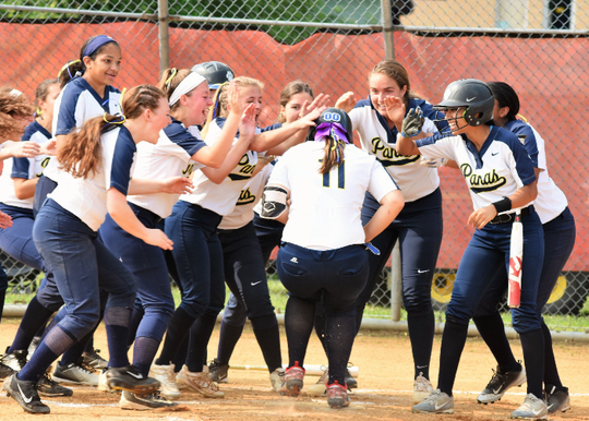 Rae Valt (11) is greeted by her Panas teammates when she touches home plate after hitting a home run.
