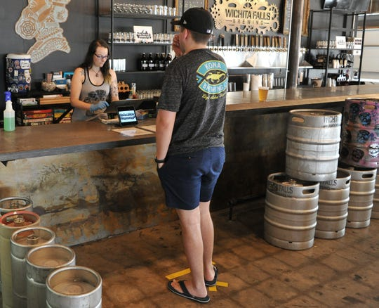 Wichita Falls Brewing Company, beertender, Katrina Thurston, served patrons after the brewery opened its doors for customers to come-in to sit instead of picking up their orders to go.