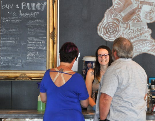 Wichita Falls Brewing Company, beertender, Katrina Thurston, centered, serves patrons after the brewery opened its doors for customers to come-in to sit instead of picking up their orders to go.