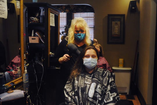 Stylist Tammy Kieffer dries Danielle Sunkel's hair at Lauren's on Maple. Barbershops and salons are working through the high demand and new protocols after reopening earlier this month.