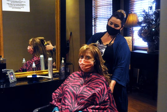 Stylist Michele Shipley works on Nora Allen at Lauren's on Maple. Barbershops and salons are working through the high demand and new protocols after reopening earlier this month.