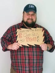 Chris Stanton, an intervention specialist at South Elementary in Morgan Local School District, holds up a sign he posted online for his students. Stanton is one of many teachers forced to teach online due to COVID-19.