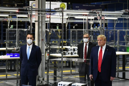 US President Donald Trump (R) tours the Ford Rawsonville Plant, that has been converted to making personal protection and medical equipment, in Ypsilanti, Michigan on May 21, 2020. (Photo by Brendan Smialowski / AFP) (Photo by BRENDAN SMIALOWSKI/AFP via Getty Images) ORIG FILE ID: AFP_1S135B