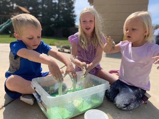 Kids do a simple science experiment outside. Camp counselors say getting outdoors is critical for kids' well-being.