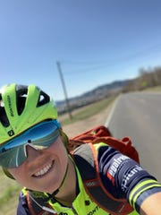 Olympic cyclist Ruth Winder takes a photo while riding delivering baked goods via bicycle in Boulder, Colorado.