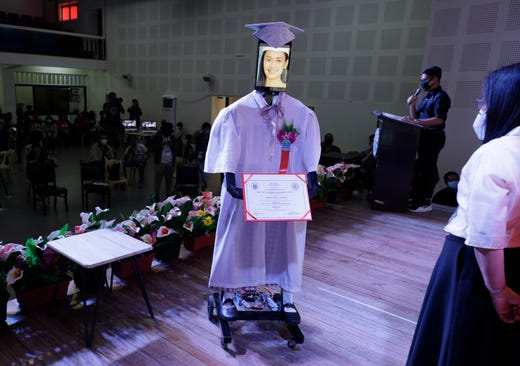 A picture of a student is seen on a tablet that is placed on a robot during an event called