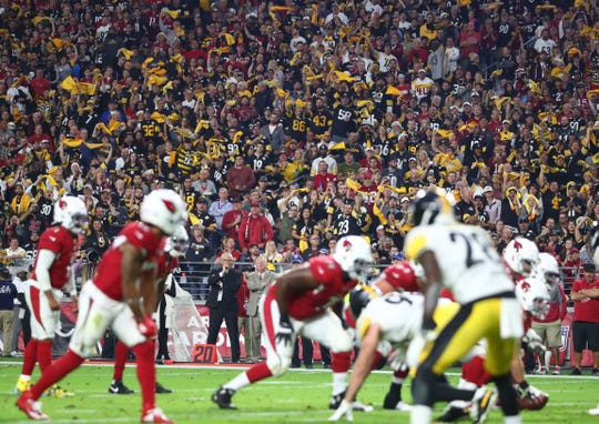 Steelers fans in the crowd wave yellow terrible towels against the Cardinals.
