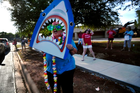 Kindergarten teacher Kathy Giron waves a shark mouth cutout as she calls to a passing student outside of Austin Elementary School on Tuesday. Students of all grades paraded by to say goodbye to their teachers at the end of the school year which had been severely altered due to the coronavirus pandemic. Since mid-March, students have only been able to interact with their teachers over online teleconference services and virtual classrooms.