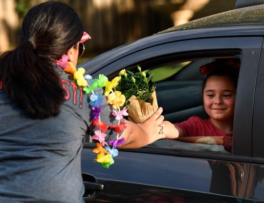 Second-grader Lauren Goodwin hands flowers to her teacher Courtney Arterberry outside of Austin Elementary School on Tuesday.