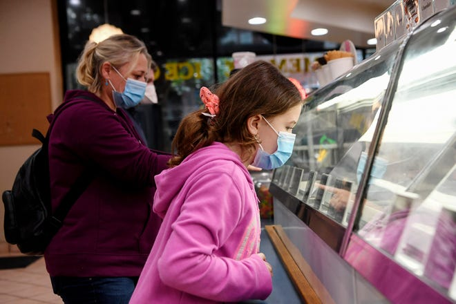 Savannah Schwoerer, of South Carolina, chooses an ice cream flavor with her mother, Birgit, and father, Thomas, at Marble Slab Creamery in Asheville May 22, 2020. The shop required customers to wear masks and was able to provide them as the family only had one mask among them.
