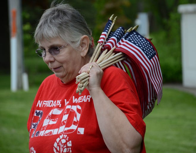 Barb Jinks carries a bundle of flags placed outside American Legion Post 257 on Friday.  Trace Christenson/The Enquirer