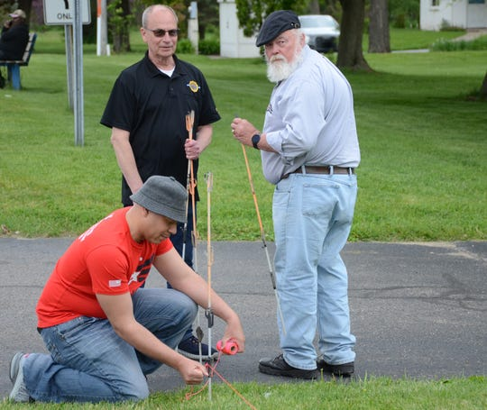 Josiah Elzy, from left, Brian Mohlman and Ken Nierman prepare a straight line for the flag placement.  Trace Christenson/The Enquirer
