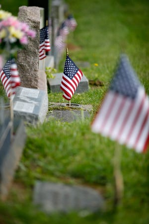 Volunteers plant flags at the gravesites of American veterans at the Pierce Township Cemetery in Clermont County, Ohio, on Friday, May 22, 2020. Volunteers from the Veterans of Foreign Wars 6770 in New Richmond met Friday evening to pay tribute to veterans ahead of the Memorial Day holiday.