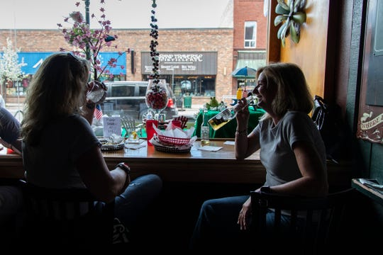 Kim Kibner of Highland, left, enjoys a beer with her friend Lena Schutz of Howell, at the U & I Lounge in downtown Traverse City on May 22, 2020.