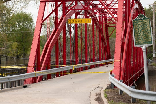 The historic Currie Parkway Bridge, which crosses the Tittabawasee River in Midland, is wrapped with yellow caution tape after massive flooding. Water had begun to recede on May 22, 2020.