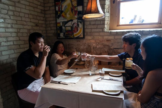 Karin Chung, center, toasts to her son Walker Chung, left, daughter Jami Chung and Mac Chung, all of Traverse City, at Trattoria Stella in Traverse City on May 22, 2020.