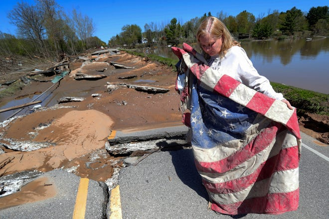 Kim Burgess unfolds a flag she recovered from the Veterans War memorial dedicated veterans and her son lance corporal Ryan Burgess who was killed in Iraq. The Veterans Memorial stood near Saginaw Rd. in Sanford Michigan on May 21, 2020. The Sanford dam that held the Tittabawassee river failed causing massive flooding destroying homes and businesses.