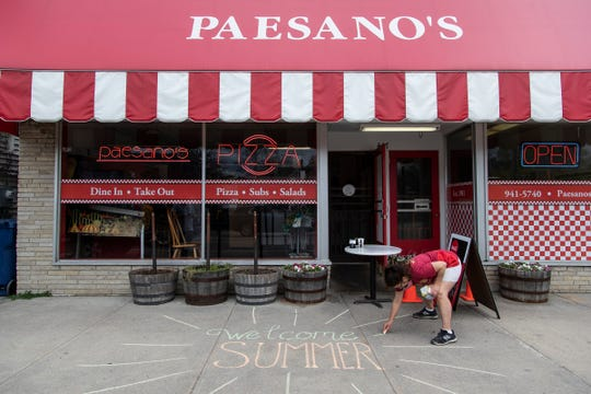 """Sue Parks, co-owner PaesanoÍs Pizzanin Traverse City, uses chalk to write a """"Welcome Summer"""" message on the sidewalk to cheer people up on May 22, 2020. Paesano's remains open for take out only."""