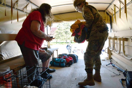 Pfc. Lydia Humphrey of the Michigan National Guard, helps evacuate Anita Wheeler, of Midland, during record flooding in Midland.