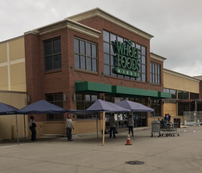 Customers practice social distancing at Whole Foods Market in Detroit on Friday, May 22, 2020.