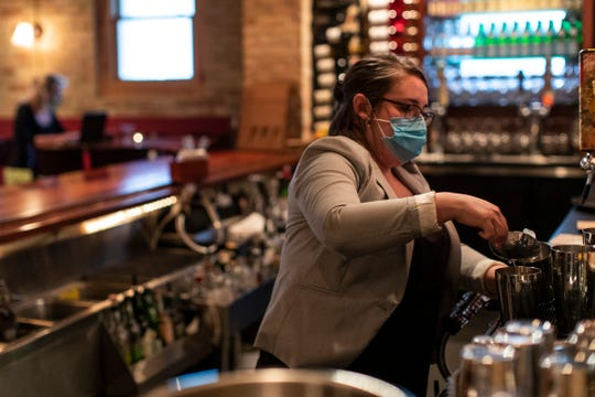 Gina Jidas mixes drinks for customers at Trattoria Stella in Traverse City on May 22, 2020.