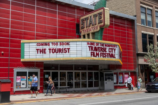 People walk by State Theatre on Front Street in downtown Traverse City on May 22, 2020.