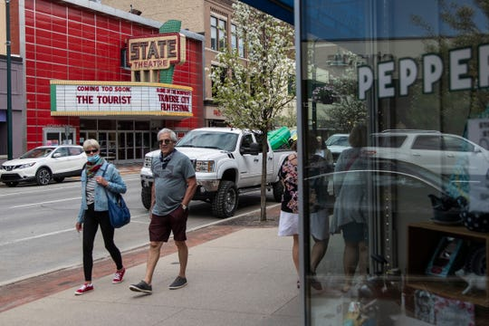 People walk on Front Street near State Theatre in downtown Traverse City on May 22, 2020.