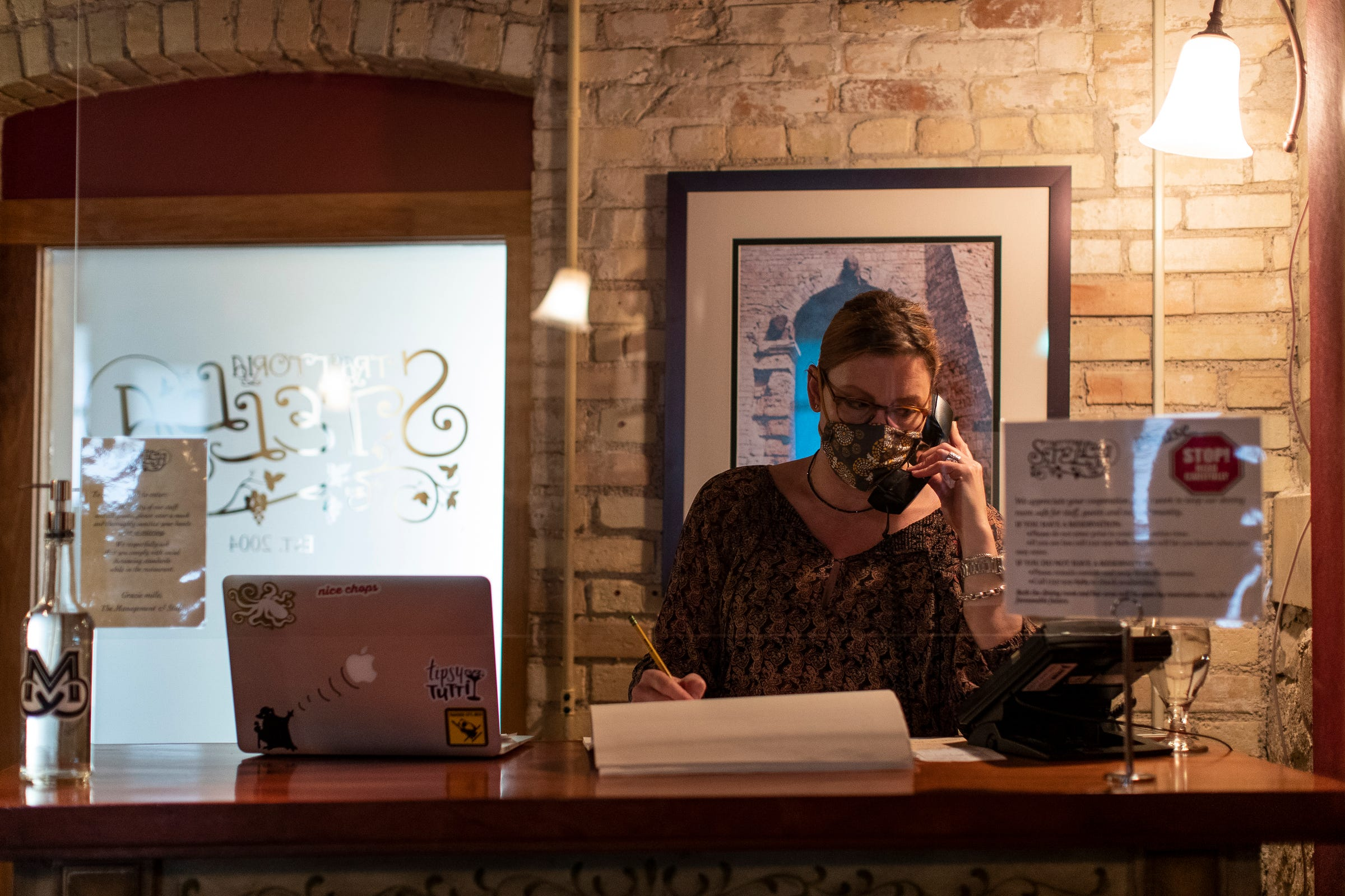 Amanda Danielson, co-owner of Trattoria Stella, answers customer calls at the restaurant in Traverse City on May 22, 2020.