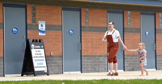 Sydney Vlaminck, passes the closed park bathrooms with her daughter, Isla, 4, both of Port Huron, as they walk to the porta-potties.