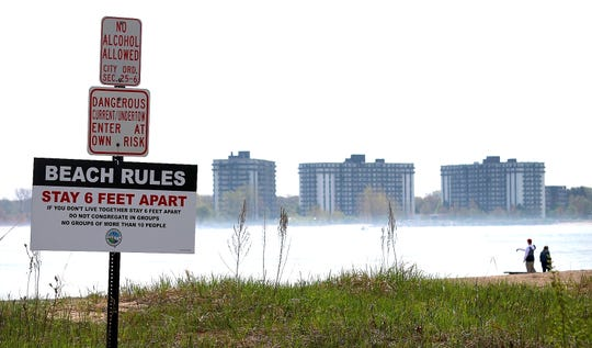 A beach-rules sign is displayed at Lighthouse Beach, Saturday morning, May 23, 2020, as Port Huron beaches are open, including, Lakeside Park beach. Visitors must follow social-distancing and group limit rules.