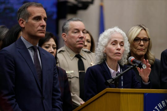 FILE - In this March 12, 2020 file photo Los Angeles County Public Health Director Barbara Ferrer, at podium, speaks at a news conference with Los Angeles Mayor Eric Garcetti, left, in Los Angeles.