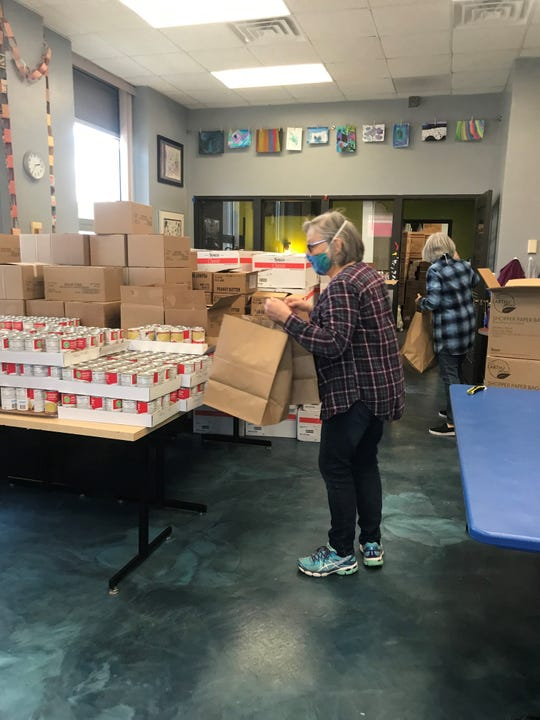 Door County Meals Cooperative volunteers organize food into weekend meal kits in the local Boys & Girls Club kitchen.