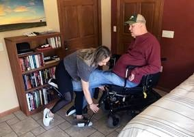 Matt Ford is seen in Verona, Wis., with his caregiver Grace Brunette. A diving accident in 1987 left Ford paralyzed in all four limbs. The pandemic has made finding caregivers even harder than usual, but Brunette now spends three nights a week at Ford's home to help with his care.