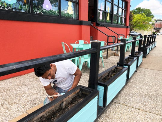 Employee Cesar Lopez paints flower boxes on Thursday afternoon to prepare for the start of sidewalk dining at Tacoholics Mexican restaurant at 122 First St. in Downtown Henderson. Tacoholics opened to on-site dining service on Friday utilizing its two indoor dining rooms, front sidewalk and side patio with tables set six or more feet apart. It is continuing to offer drive-through pickup orders from its ChimiiTruck parked in its side parking lot.