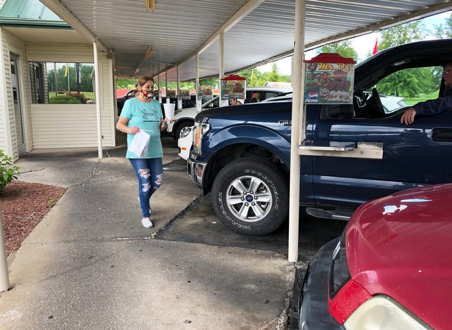 Veteran carhop Missy Simmons delivers lunch to a customer at Mr. D's drive-in at 1435 S. Green St. in Henderson on Thursday. The drive-in, owned by the DeLamar family since 1982, has been popular for many years but has been operating virtually at capacity during the two-month-long coronavirus pandemic.