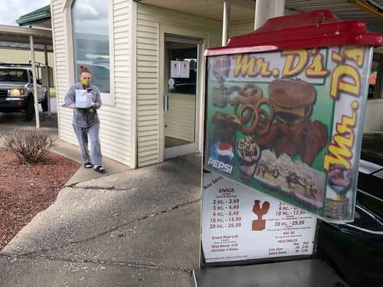 Carhop Briana Neblett delivers lunch to a customer at Mr. D's drive-in at 1435 S. Green St. on Thursday. The drive-in, owned by the DeLamar family since 1982, has been popular for years but has been operating virtually at capacity during the two months of the coronavirus pandemic.