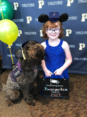 Hadley Jo Lange, a 7-year-old Louisville girl who has epilepsy and suffers seizures, is pictured alongside her service dog, Ariel, after graduating from kindergarten at St. Patrick Catholic School in Louisville, Kentucky.